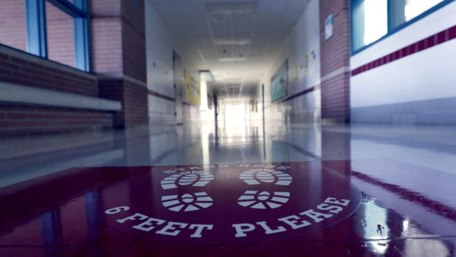 The floor of an empty hallway at Stephens Elementary School in Rowlett bears a social distancing reminder on July 22.