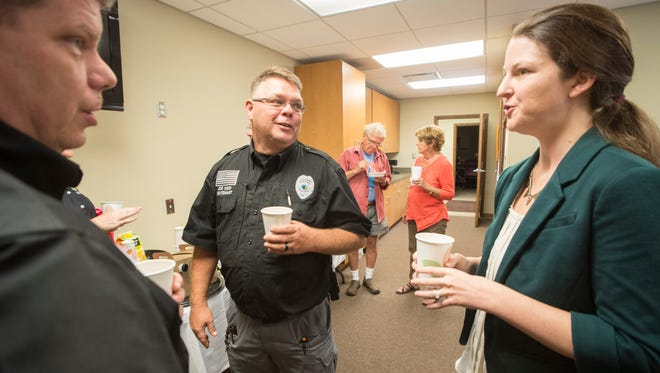 Jessica Trotman talks with Black Mountain police lieutenants Joe Kidd, center, and Rob Austin at a reception held in her honor at town hall Aug. 31.