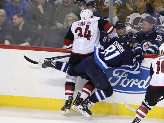 Arizona Coyotes' Zac Rinaldo (34) hits Winnipeg Jets' Kyle Connor (81) against the boards during first period NHL hockey action in Winnipeg, Manitoba Tuesday, Feb. 6, 2018. (Trevor Hagan/The Canadian Press via AP)