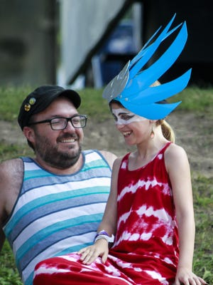 Empire of the Sun music fan Olivia Baird, 8, of Chicago, hangs out with her dad Michael Sunday, July 12, 2015, during the final evening of the Common Ground Music Festival at Adado Riverfront Park in downtown Lansing.