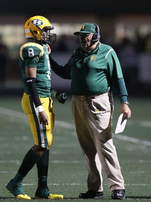 Farmington Hills Harrison coach John Herrington talks with Noah Hendricks on the sidelines during the first half of Harrison's 39-0 win over Berkley, allowing Herrington to set the record for most wins in state history on Friday, Oct. 13, 2017, at Harrison.