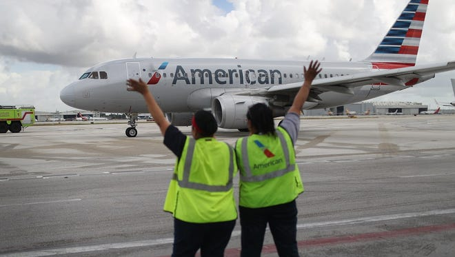 Workers wave as American Airlines Flight 903 prepares for take off in Miami  on Sept. 7, 2016,  for Cuba.