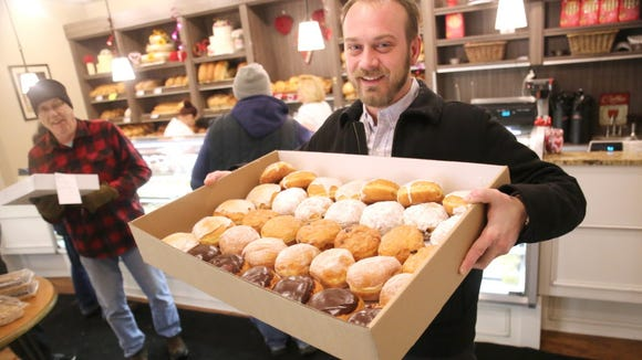 Patrick Barrett, of Bay View, holds his box full of an assortment of Paczki at Canfora Bakery.