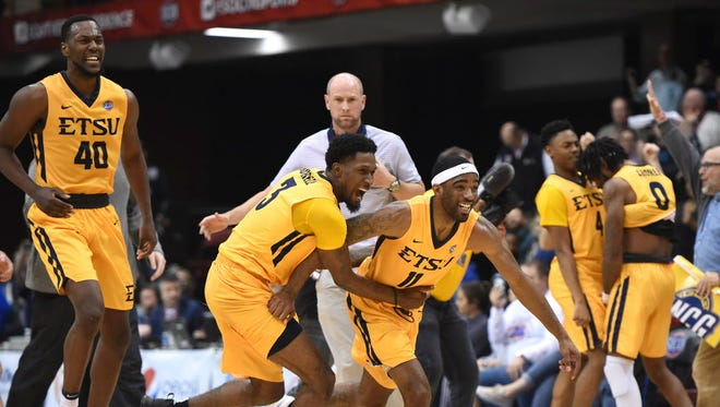 East Tennessee State's forwards Tevin Glass (40), David Burrell (3) and guards Desonta Bradford (11), Jason Williams (4) and T.J. Cromer (0) celebrate their 79-74 win over UNC Greensboro.