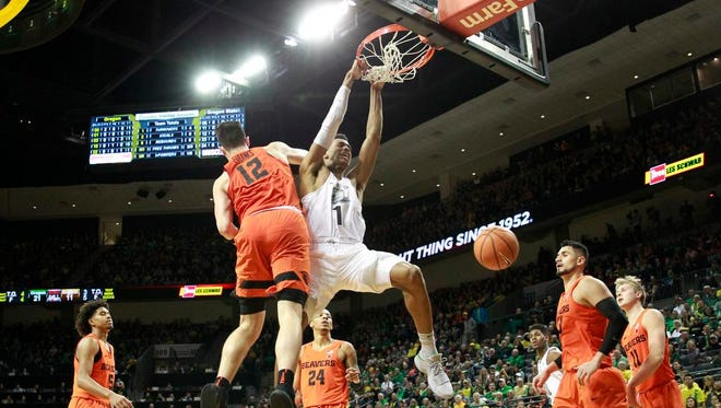 Oregon's Kenny Wooten, center, dunks over Oregon State's Drew Eubanks, left, during the first half of an NCAA college basketball game Saturday, Jan. 27, 2018, in Eugene, Ore. (AP Photo/Chris Pietsch)