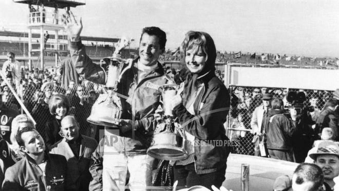 FILE - In this Feb. 26, 1967, file photo, Mario Andretti, of Nazareth, Pa., holds up his trophies with his wife, Dee Ann, after he won the Daytona 500 auto race at Daytona Beach, Fla. Dee Ann Andretti, the wife of legendary driver Mario Andretti and matriarch of one of the most prominent families in motorsports, died Tuesday, July 3, 2018. She was 76. Dee Ann Andretti mostly stayed in the background and raised their three children while her husband became one of the world's most successful and famous race car drivers. (AP Photo)