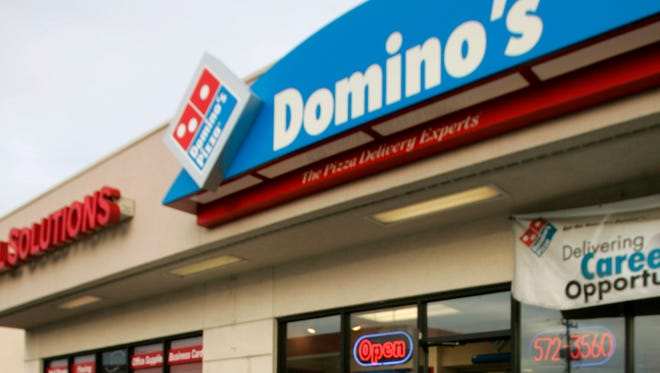 A Domino's Pizza delivery driver heads to his car with orders in Sandy, Utah.