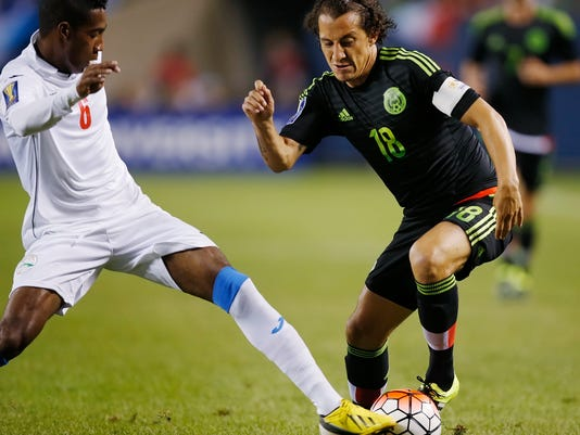 Mexico midfielder Andres Guardado (18) battles Cuba defender Yaisnier Napoles (6) during the first half of a CONCACAF Gold Cup soccer match, Thursday, July 9, 2015, in Chicago. (AP Photo/Andrew A. Nelles)