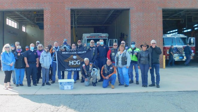 Taking part in the donation were, far left, Sheila Duncan, founder of The Kennek Foundation; left of the banner, Lt. Steve Morrison, Billerica Fire Department; right of the banner, Firefighter Andrew Pierce, Billerica Fire Department; Eric Lekberg, kneeling with Trouble the Dog; and fellow members of the Merrimack Valley Harley Owners Group.