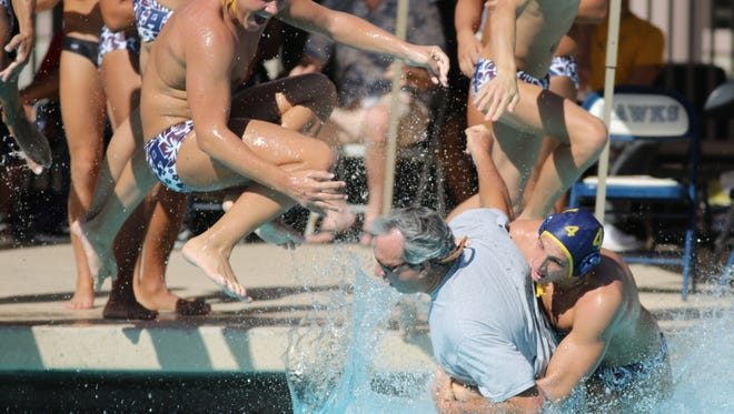 The La Quinta water polo team take their coach into the water after winning the DVL title game against Xavier Prep on Saturday, October 21, 2017 in La Quinta.
