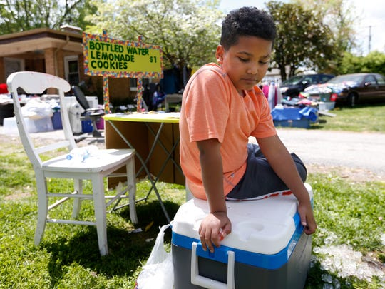 Tristan Jacobson, 9, sits on a water cooler in front
