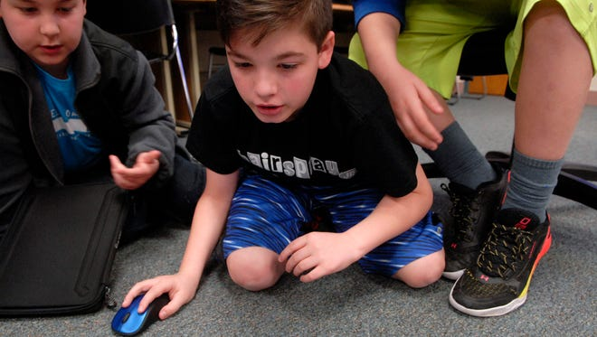 Student Ethan Biggs, center, works on a video project as Logan Hart looks on at Jonathan Jennings Elementary School's tech support team.