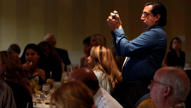 "Javier Fuller from Online Solutions takes pictures at the ""Southwest Florida Mayors Going Global"" panel discussion Wednesday at The Landings community Wednesday in Fort Myers."