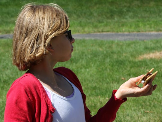 """Brooklyn Perkins samples """"the best s'more I ever had"""" that she made in a solar s'more oven on July 6 during a weeklong Cardboard Creations camp at Wauwatosa's Suburban YMCA."""