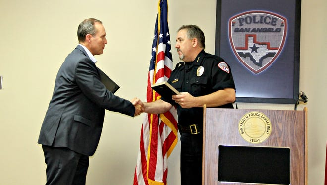 Local news director David Wagner is presented with a merit award by San Angelo Police Chief Frank Carter.