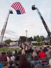 The American flag flies suspended from two ladder trucks