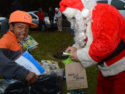 ANI Grant Sheriff Department J.T. Chatman (left), who was excited to see Santa Claus show up at his home, holds nearly all the gift Santa Claus and and the Grant Parish Sheriff's Office brought him Tuesday, Dec. 23, 2014. In addition to toys, he received a