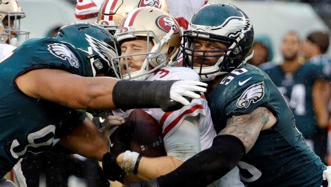 Philadelphia Eagles' Destiny Vaeao (97) and Chris Long (56) take down San Francisco 49ers' C.J. Beathard during the second half of an NFL football game, Sunday, Oct. 29, 2017, in Philadelphia.