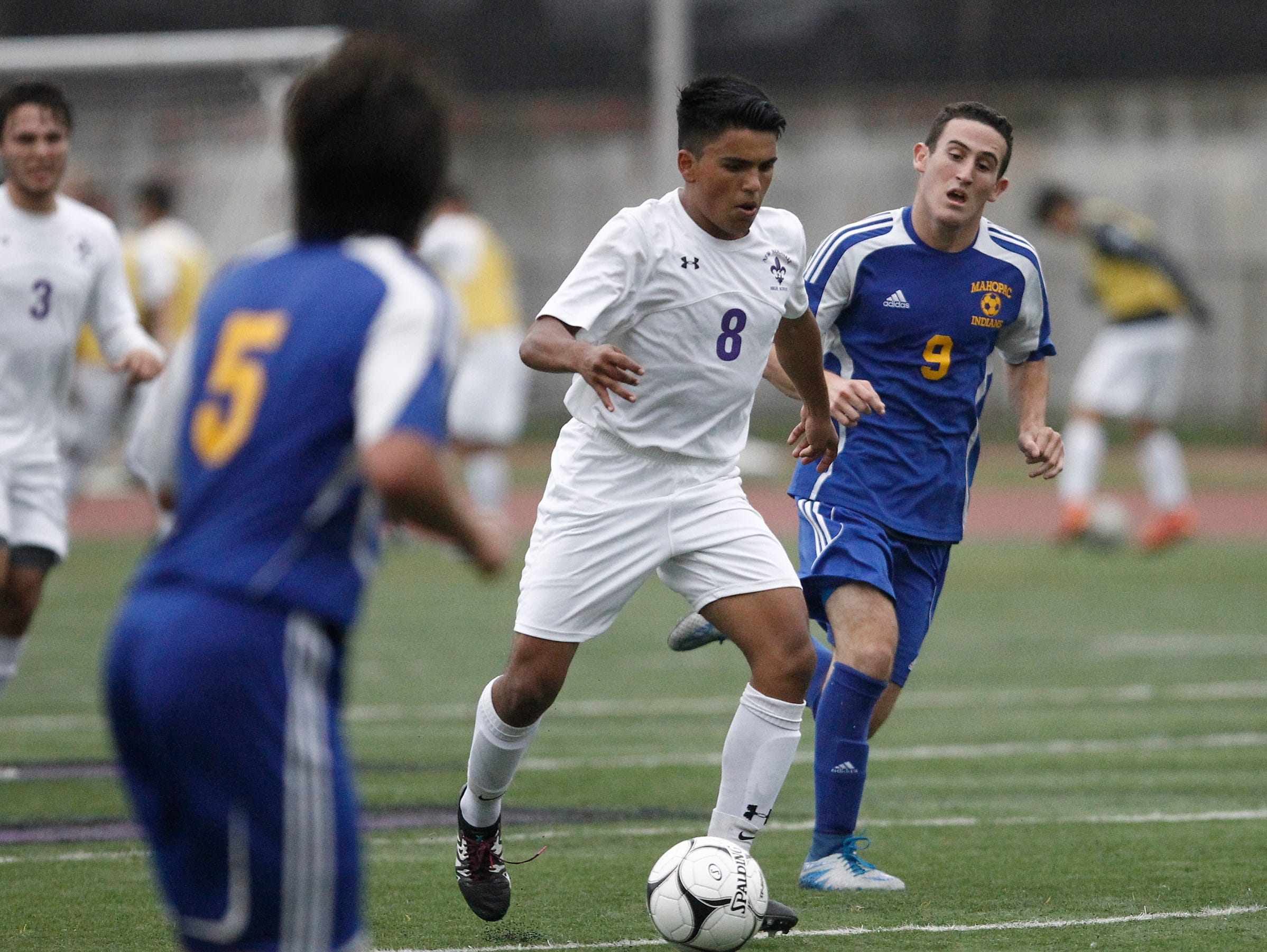 New Rochelle's Omar Espinoza (8) works the ball at mid-field as Mahopac's Max Lichtman (9) defends during the boys soccer Class AA first round at New Rochelle High School in New Rochelle on Thursday, October 20, 2016. New Rochelle advances with their 2-0 win.