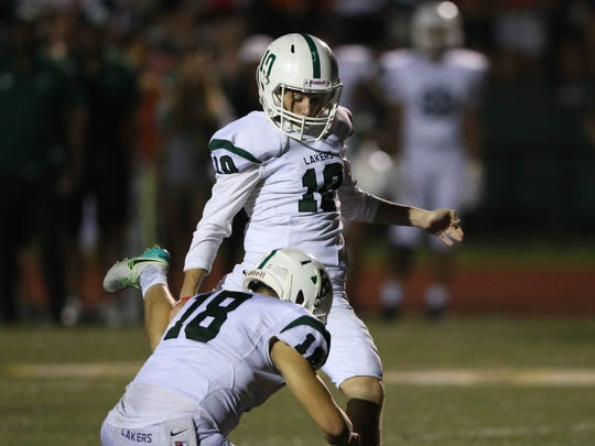 West Bloomfield's Nick Seidel holds for Nick O'Shea, who kicks an extra point in the third quarter against Rochester Adams, Friday, Sept. 22, 2017 in Rochester.