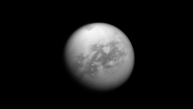 Titan's Kraken Mare, a large sea of liquid hydrocarbons, is visible as a dark area near the top of the image.