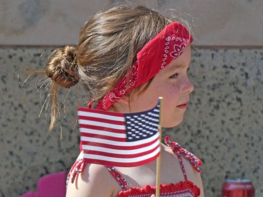 Anna Ankrum, 7 years old of Mansfield, patriotically waves a flag as the Memorial Day parade goes by Monday morning.
