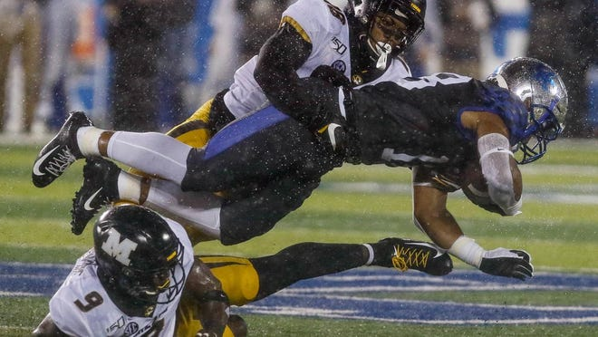 Missouri's Joshuah Bledsoe (18) and Tyree Gillespie (9) tackle a Kentucky receiver during a Southeastern Conference game Oct. 26, 2019, in Lexington, Ky.