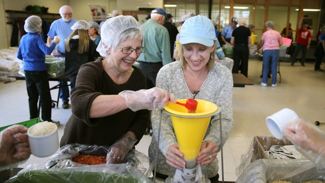 Norma Brimstein of Irondequoit, left, and Debbie Dwyer of Penfield volunteered their time to help Stop Hunger load 57,000 individual meal packets at the Penield Community Center as part of the Stop Hunger program.