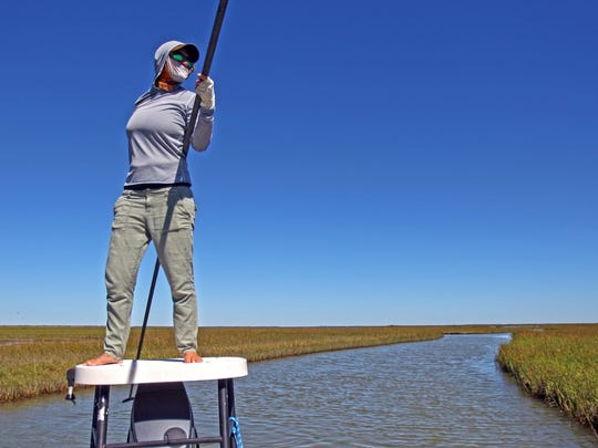 By October, fly anglers were enjoying calm bays and clear tides. Here, fly guide Kacee Bones uses a push pole to navigate a narrow path through marshes north of Rockport.