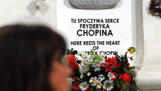 A woman sits in front of the shrine where the heart of Polish-born composer Frederic Chopin rests in the Church of the Holy Cross, in Warsaw, Poland on July 28, 2008. Polish medical experts say Wednesday, Sept. 17, 2014, that the preserved heart of 19th century composer shows signs of tuberculosis and possibly some other lung disease.