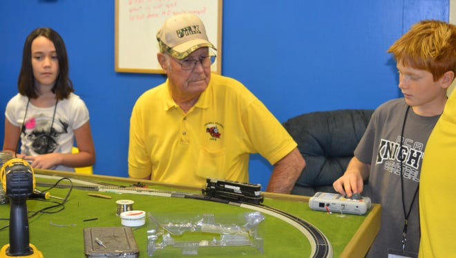 Mitchell Mosura (right), 9, controls the speed of a model train on a track at the Alexandria T.R.E.E. House Children's Museum's Junior Engineer Camp on Tuesday. Bill Taylor (center) with the Rockwell Railroad crew teaches Mitchell and other students, including 9-year-old Brynna Street (left), how to operate two trains on the same track on the first day of the camp.