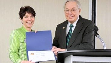 Radisson Hotel General Manager Michele Donegan accepts the Paul Harris Fellow award from Corning Rotarian Dick Pope.