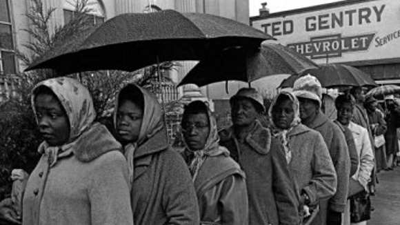 African Americans wait in line to vote after the Voting Rights Act becomes a reality in 1965, with the Justice Department helping to register voters.
