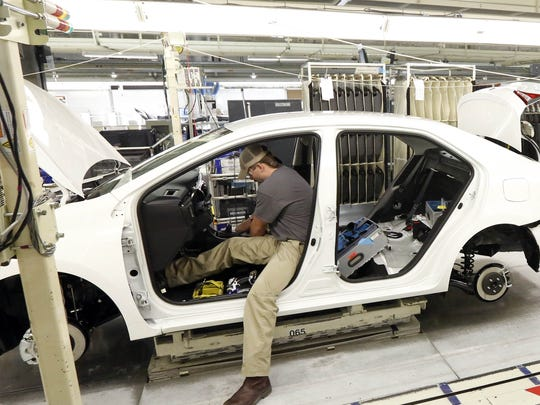 In this 2015 file photo, technicians work on a Corolla