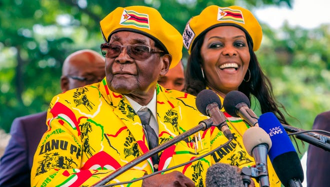 Zimbabwe's President Robert Mugabe, left, addresses party members and officials gathered at his party headquarters to show support to Grace Mugabe, right, becoming the party's next vice president after the dismissal of Emerson Mnangagwa Nov. 8, 2017.
