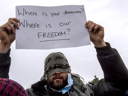 An Iranian migrant with sewn lips, holds a placard