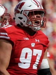 Badgers defensive end Isaiahh Loudermilk reacts after