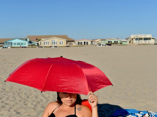 Rachel Ruiz, of Oxnard, peers out at the surf at Mandalay Beach in this file photo. The beach front zone in Oxnard has an especially high concentration of short-term rentals.