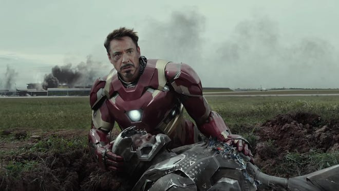 "Tony Stark (Robert Downey Jr.) sits by a fallen War Machine (Don Cheadle) in ""Captain America: Civil War."""