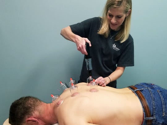 Veronica Ashlock works with a patient's back through