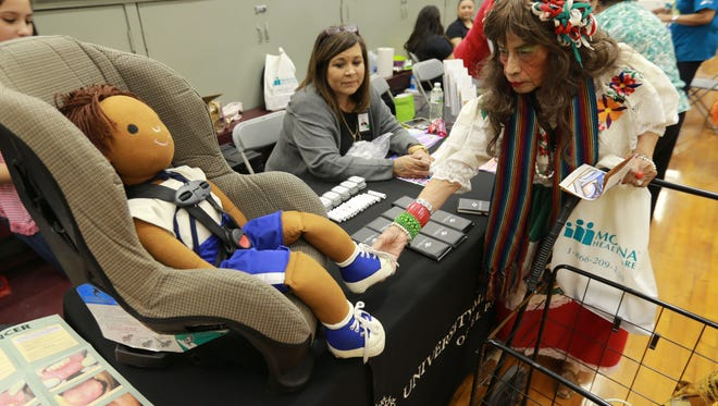 Martha Edward reached to touch a doll used by Anna Red of University Medical Center to teach about child car seat safety at the Celebre Segundo Barrio Feistival Health Fair and Family Day.