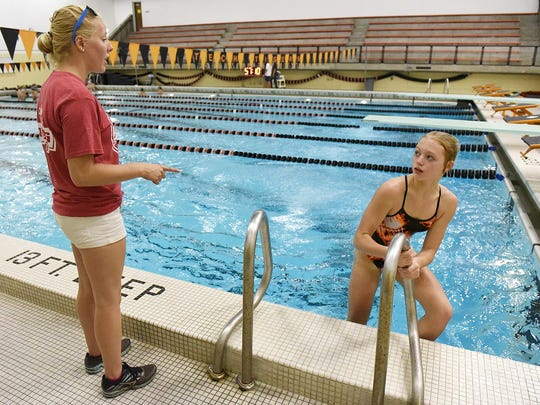 St. Cloud Tech diving coach Chelsey Bethke gives pointers to diver Meredith Matchinsky as she comes out of the water after a dive Wednesday at practice.