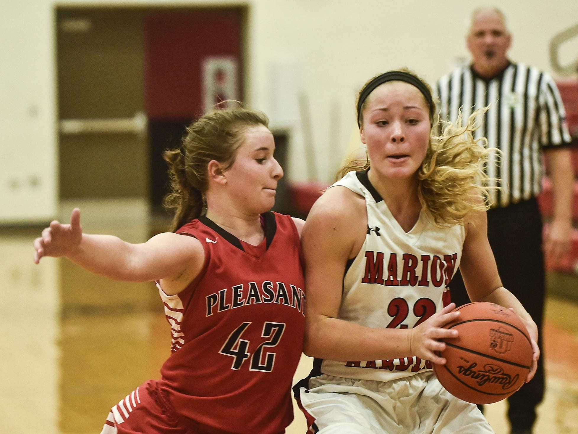 Marion Harding's Fallyn Stephens looks for a way around Pleasant's Jaden Mauk during the Marion Harding vs Pleasant basketball game on Friday.