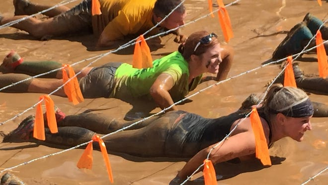 Stephanie Nottling (green shirt) crawls under barbed wire in the Tough Mudder.