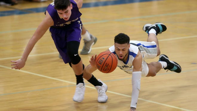 Olympic's Jaiden Mosley, right, battles Ryan Hecker of North Kitsap for a loose ball Friday at Olympic. Mosley scored 18 points to lead the Trojans to a 55-50 win.