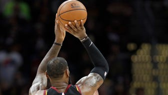 Cleveland Cavaliers' LeBron James shoots a game-winning three-point shot over Indiana Pacers' Thaddeus Young at the buzzer, breaking a 95-95 tie.