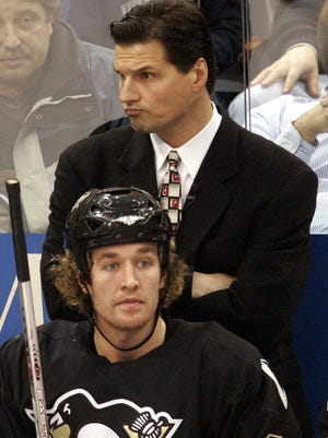 Former Pittsburgh Penguins coach Eddie Olczyk watches the first period behind Penguins' Ryan Malone on the bench against the  Minnesota Wild Thursday, Dec. 8, 2005, in Pittsburgh