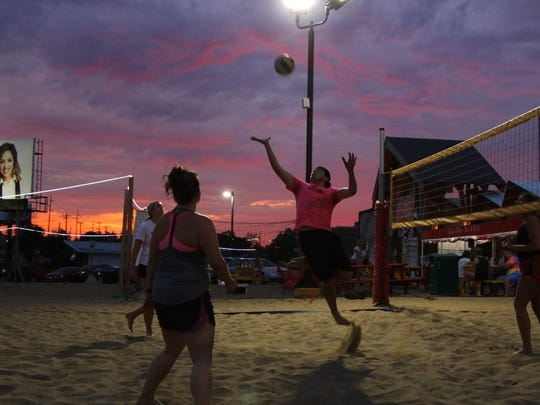 Sand volleyball players play a sunset game, Tuesday, June 13, 2017, at Spare Time Entertainment Center in Lansing.
