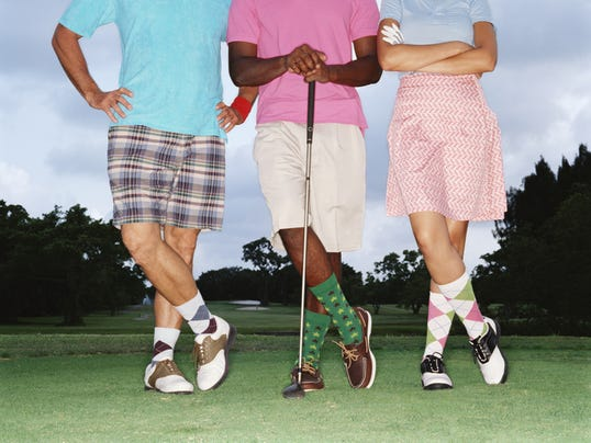 Three golfers standing in row on golf course, low section
