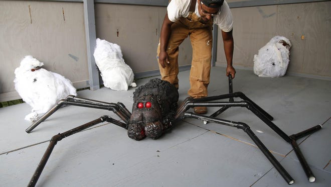 Justin Gunn assembles an oversized spider at Insanity Farms, a Halloween attraction in Tulsa, Okla., on Sept. 8.